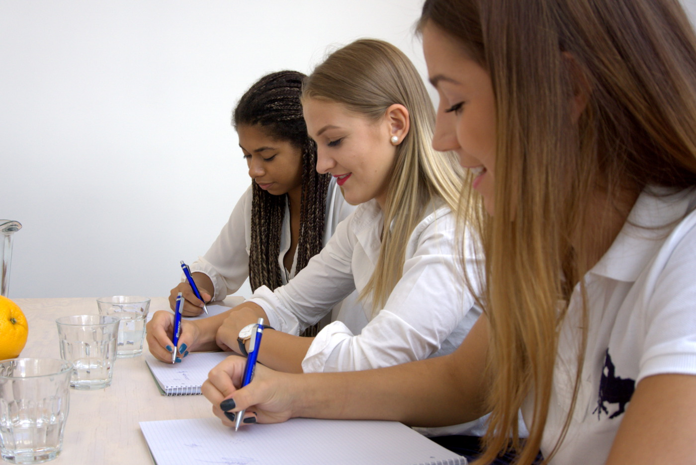 3 Junge Frauen arbeiten an einem Tisch