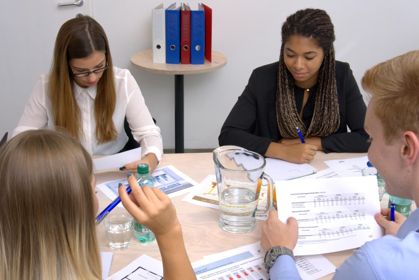 4 junge Leute arbeiten gemeinsam an einem Tisch