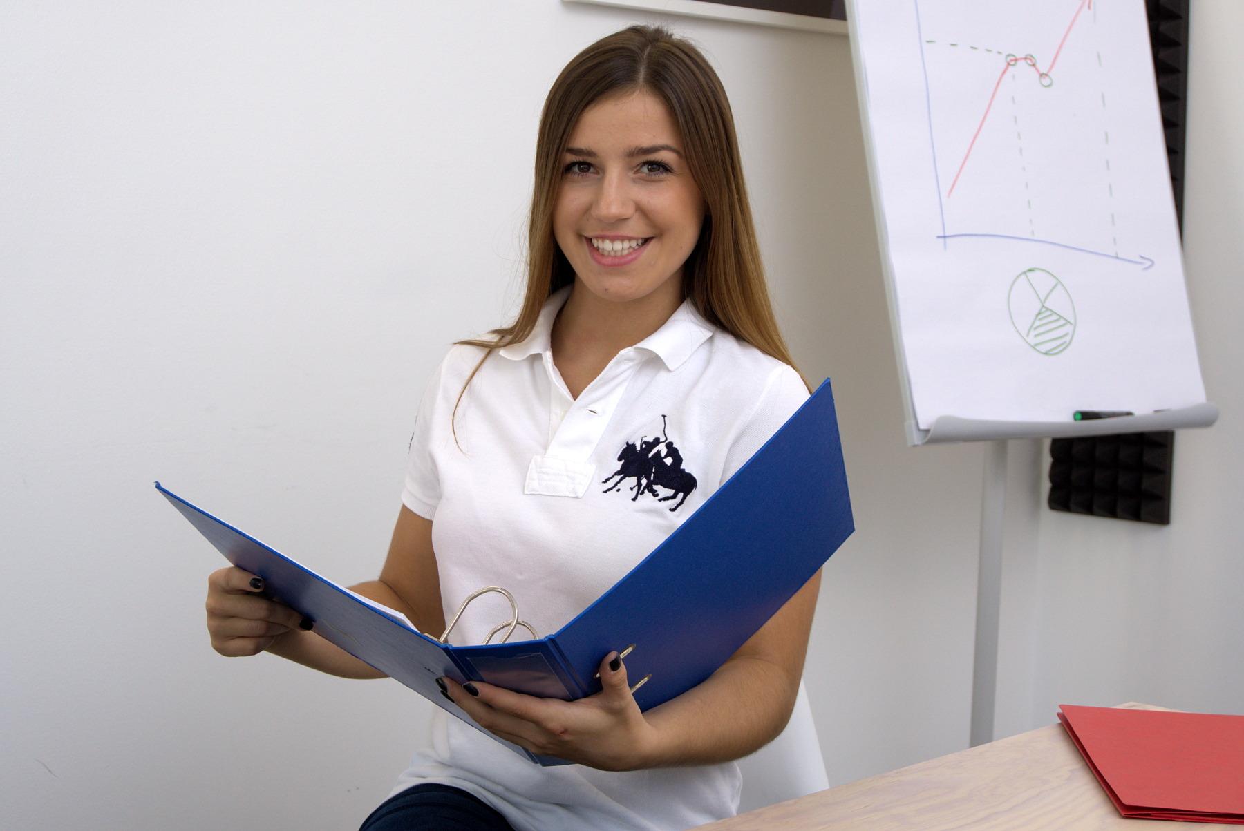 Frau mit Aktenordner lächelt
