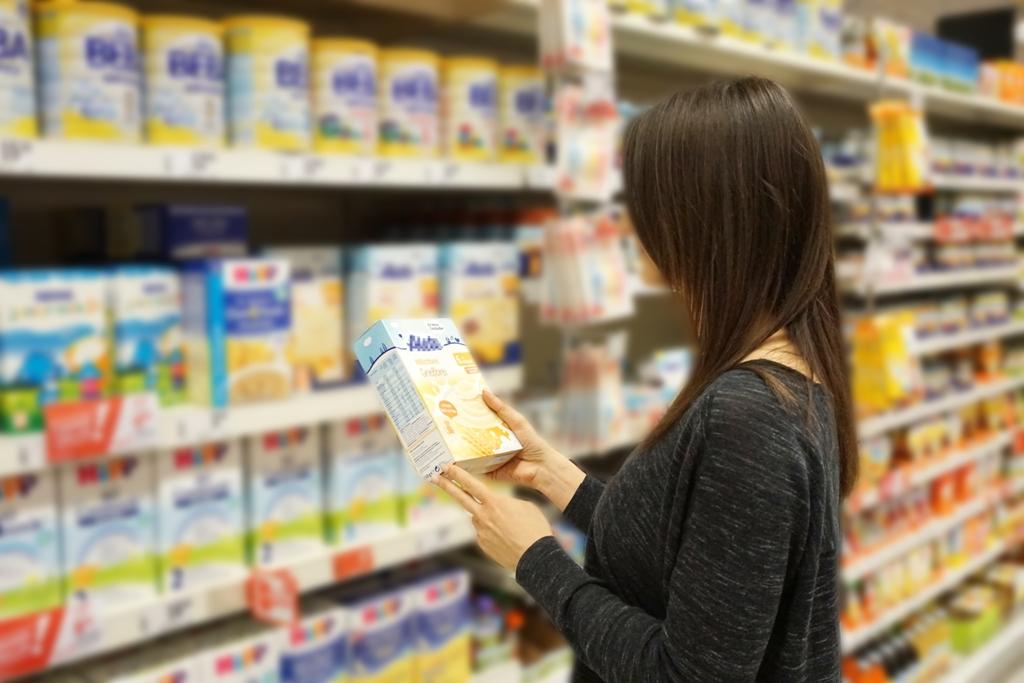 Frau prüft Zutaten / Inhaltsstoffe einer Packung