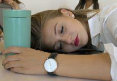 Frau schläft auf Laptop im Büro