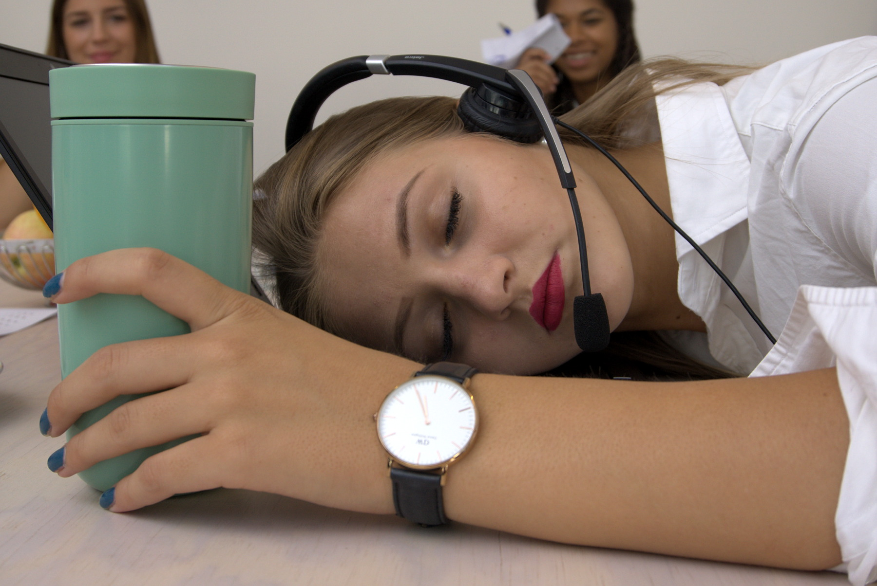 Junge Frau schläft mit Headset auf ihrem Laptop