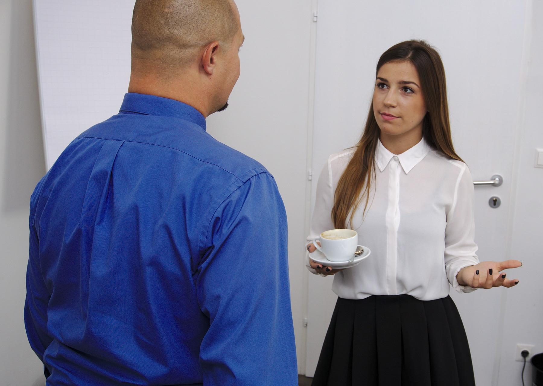 Frau mit Tasse unterhält sich mit Mann