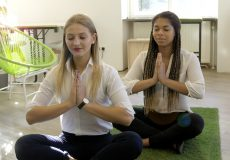 Zwei junge Frauen machen Yoga im Büro