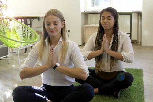 Zwei-junge-Frauen-machen-Yoga-im-Buero