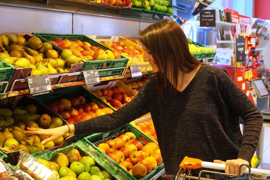 Junge Frau kauft frisches Obst