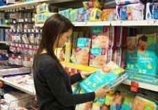 Frau kauft im Supermarkt Windeln