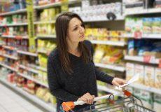 Frau mit Einkaufsliste im Supermarkt