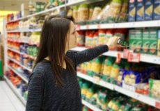 Frau nimmt Lebensmittel aus Supermartkregal / Einkauf