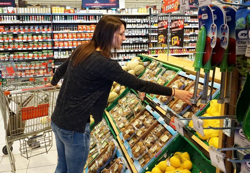 Junge Frau nimmt Obst aus Supermarktregal