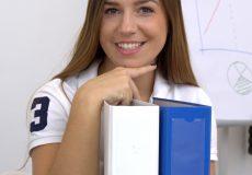 Frau posiert mit Aktenordnern und lächelt