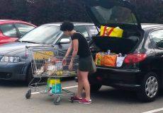 Frau räumt Einkäufe in das Auto