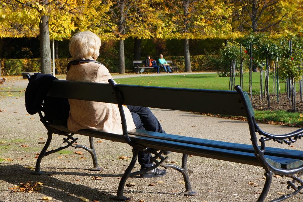 Herbst – Frau sitzt auf Parkbank