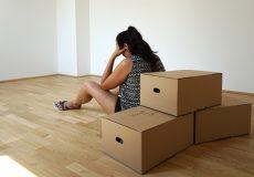 Junge Frau sitzt frustriert vor Umzugskartons