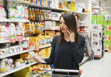 Junge Frau telefoniert während dem Einkaufen