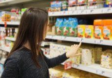 Frau vergleicht Preise im Supermarkt