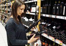 Frau vergleicht 2 Weinflaschen
