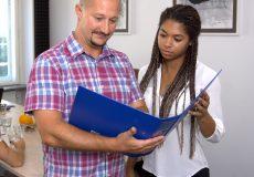 Geschäftsleute lesen gemeinsam in einem Aktenordner