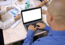 Geschäftsmann tippt während Meeting auf seinem Laptop