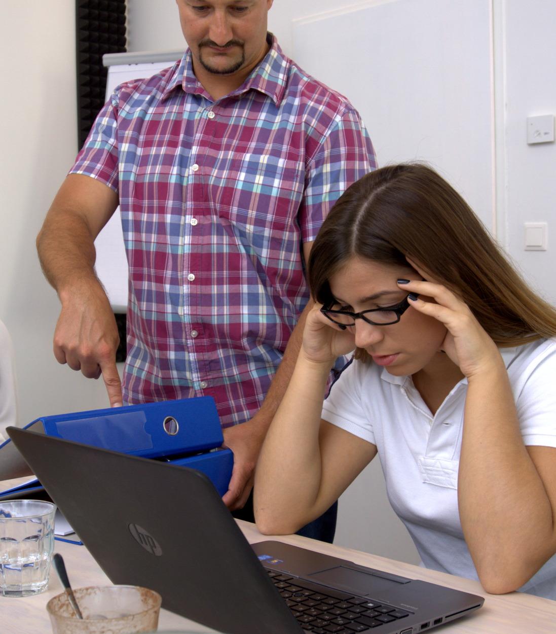Junge Frau im Büro ist überfordert / genervt – zu viel Arbeit