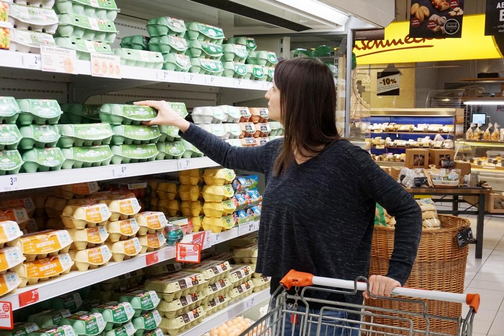 Junge Frau kauft Eier im Supermarkt