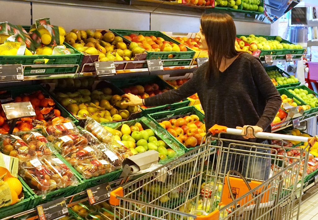 Junge Frau kauft Obst im Supermarkt