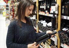 Junge Frau kauft Wein / Weinflasche
