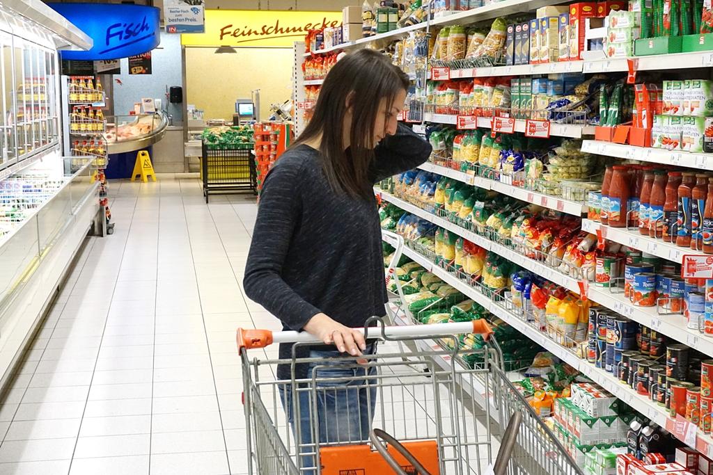 Junge Frau steht vor einem Supermarktregal