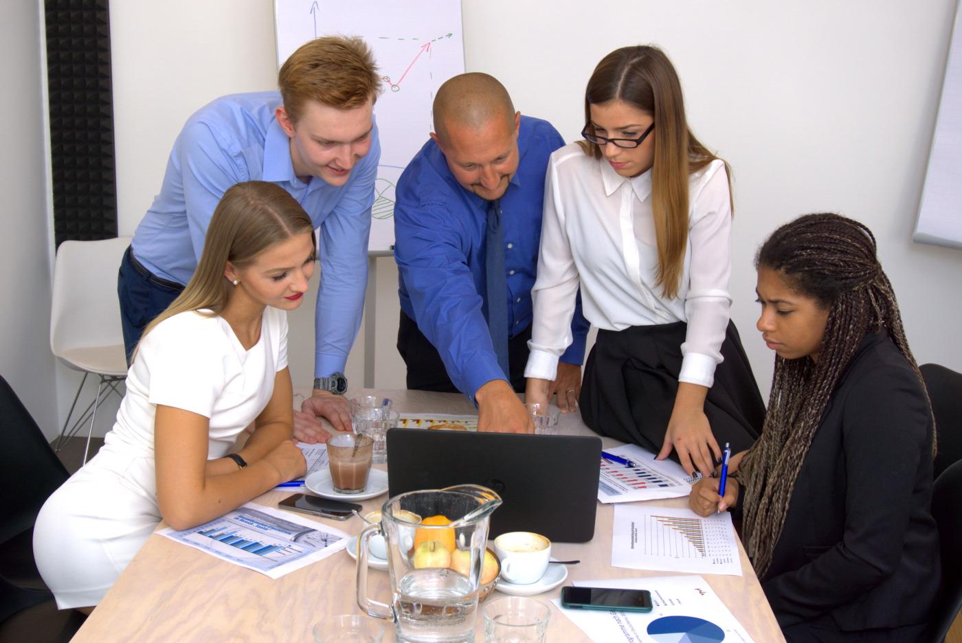 Startup Team arbeitet gemeinsam an einem Laptop – Teamarbeit