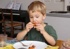 Kind beim Pizzaessen
