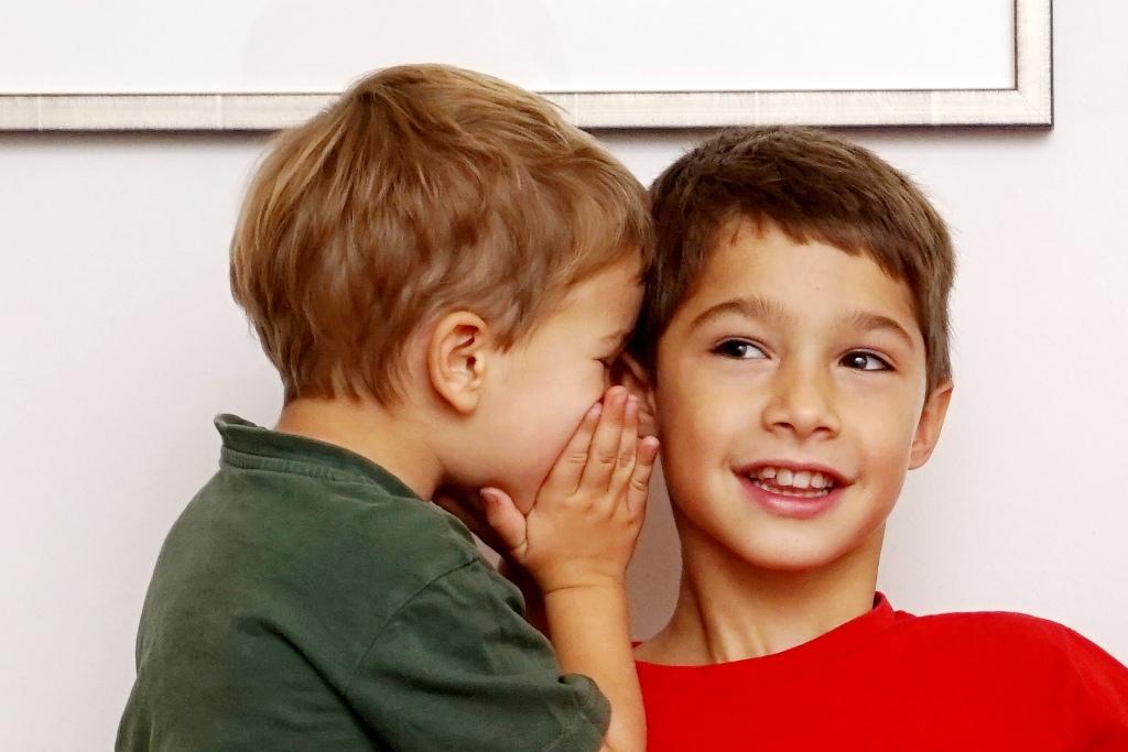 Kind flüstert anderem Kind in das Ohr