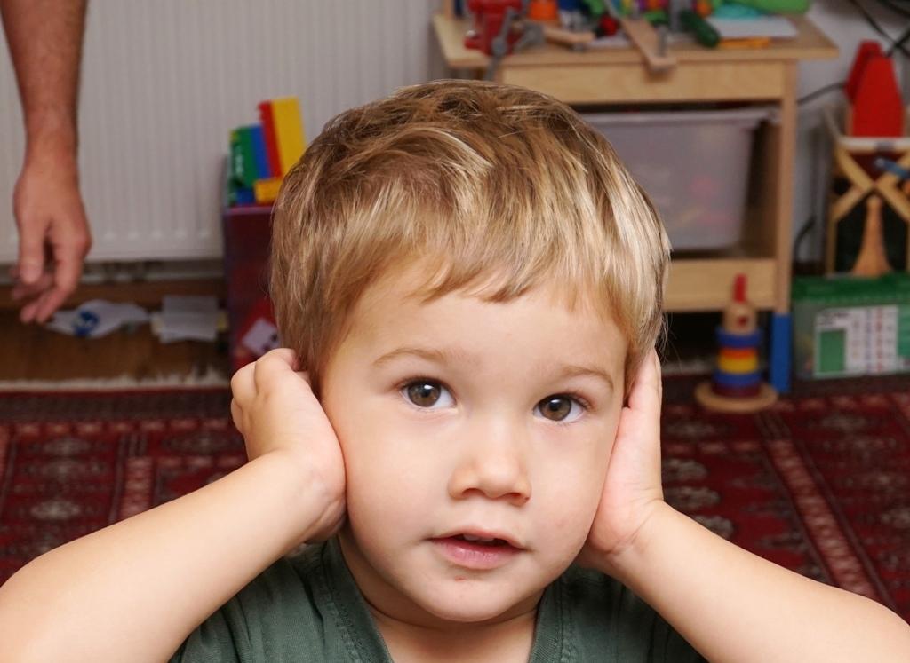 Kleines Kind hält sich die Ohren zu