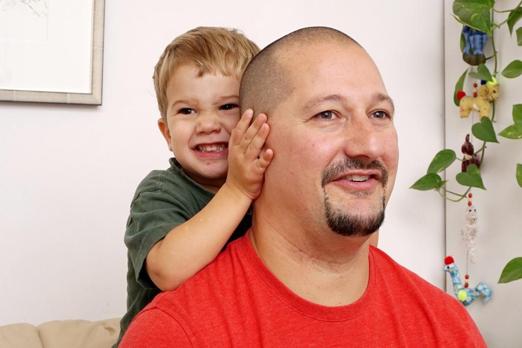 Kleines Kind hält Papa die Ohren zu
