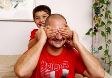 Kind hält Papa Augen und Ohren zu