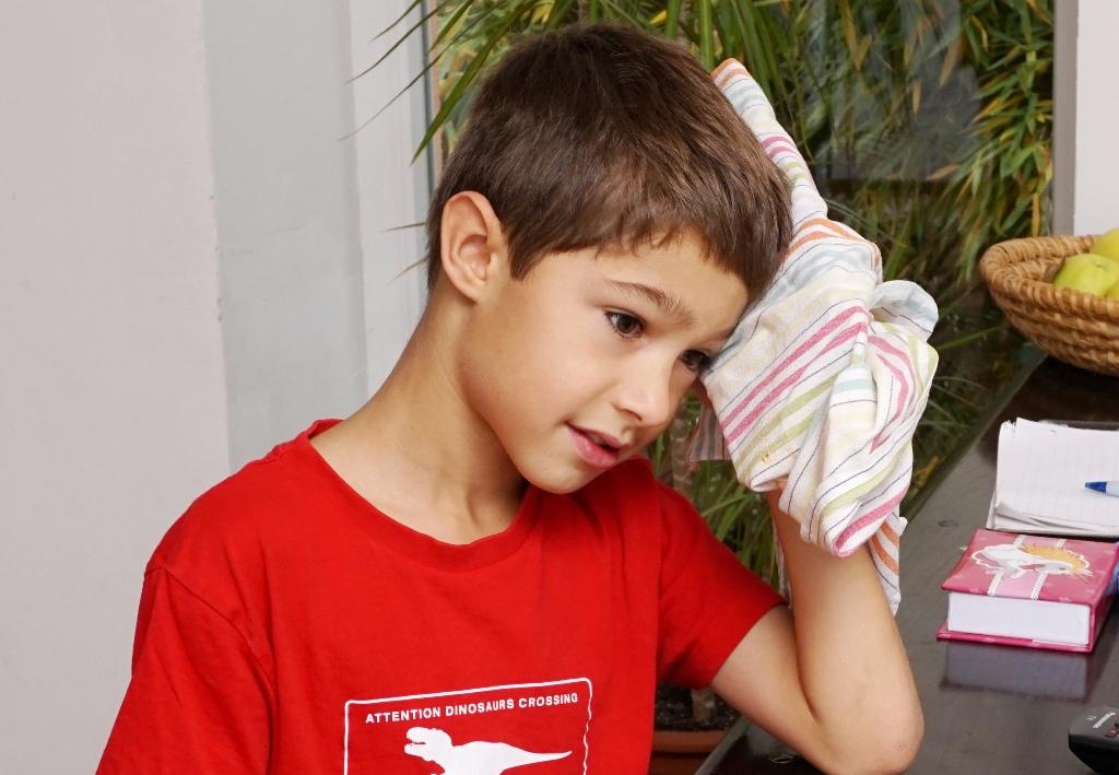 Kind hält sich Eisbeutel an den Kopf