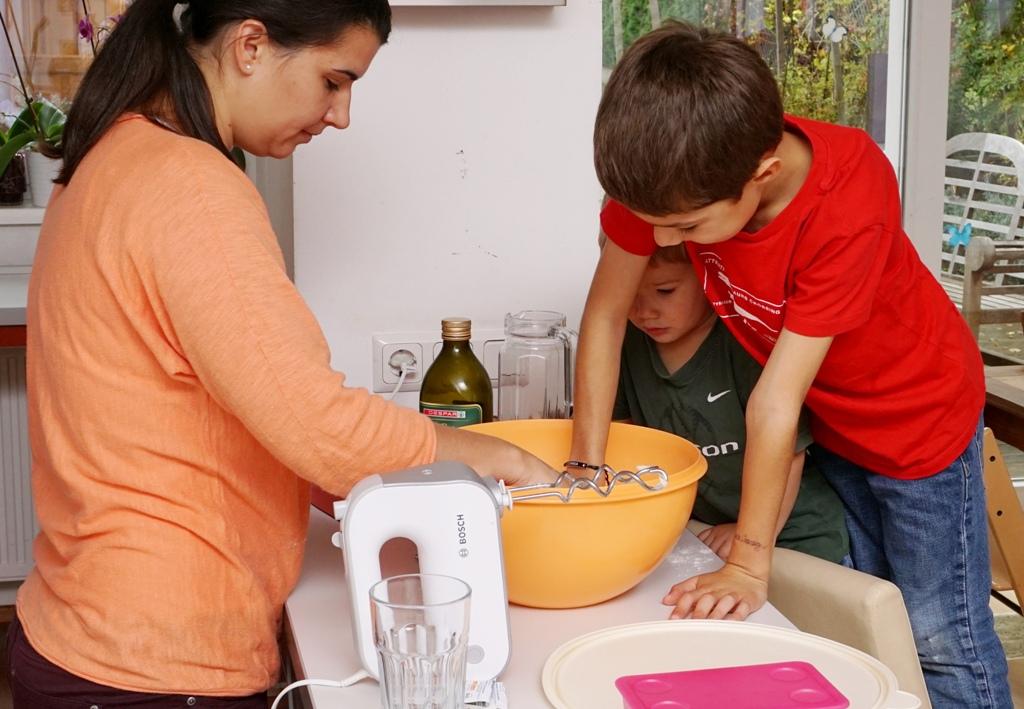 Kinder helfen Mama beim Teig kneten
