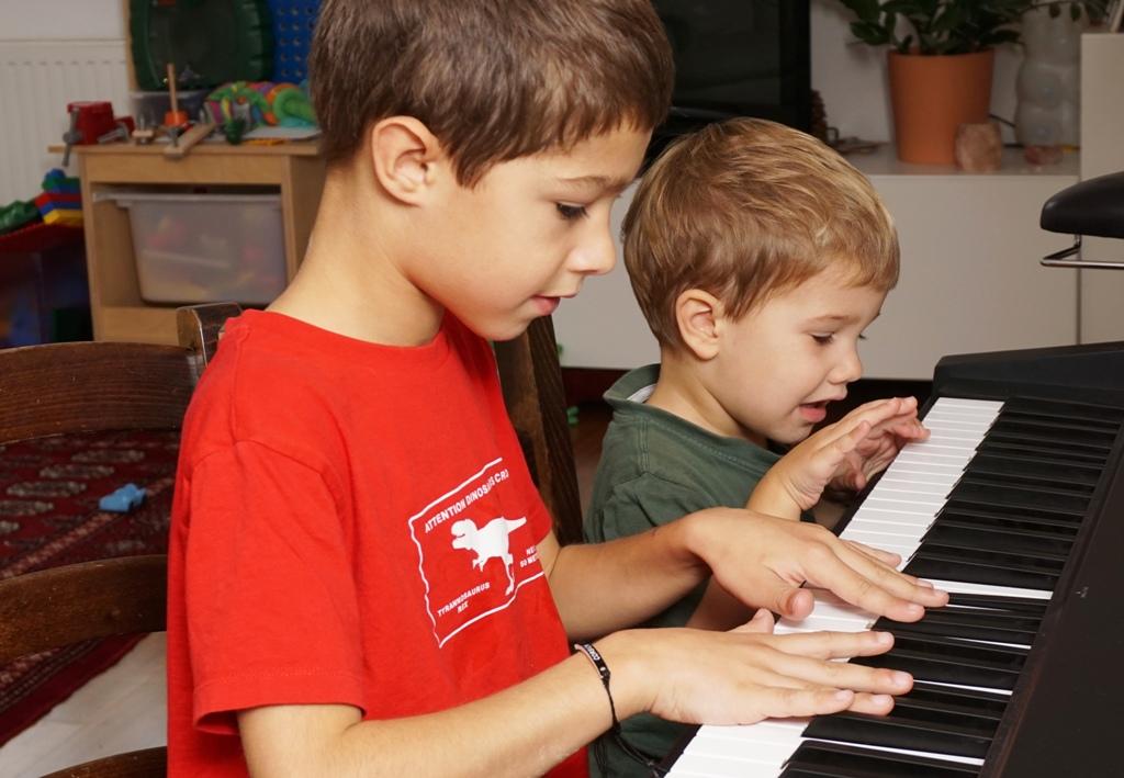 Kinder spielen gemeinsam Klavier