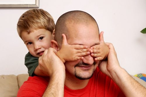 Kind hält Papa die Augen zu