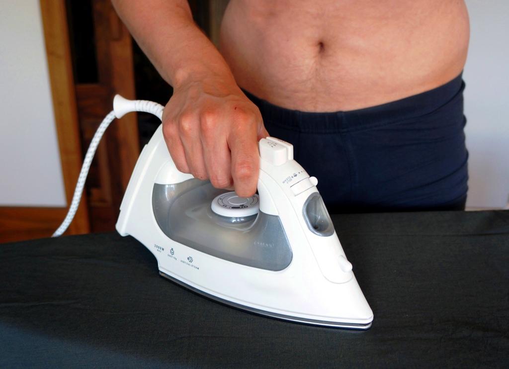 Mann beim Bügeln