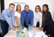 Multikulturelles Team steht gemeinsam hinter Tisch