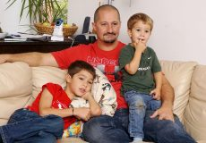 Vater und Kinder sitzen auf einer Couch