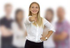 Junge Frau posiert vor Menschengruppe